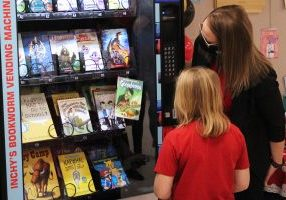 Kenzie's new Goosebumps book falls to the bottom of the vending machine.